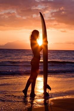 Γυναίκα με σανίδα του σερφ στο  ηλιοβασίλεμα
